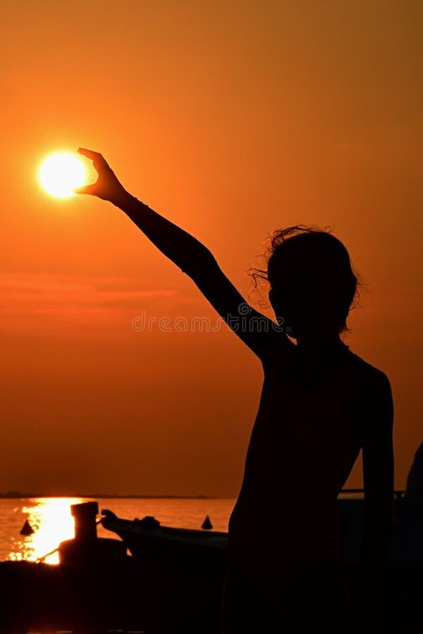 Silhouet van de kleine zon van de meisjesholding tijdens zonsondergang boven jachthaven, deel van motorboot een zichtbaar op rech royalty-vrije stock afbeelding