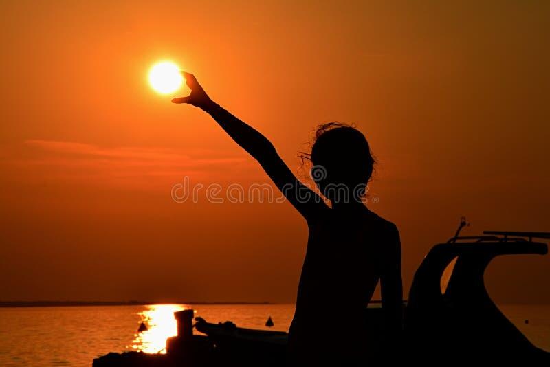 Silhouet van de kleine zon van de meisjesholding tijdens zonsondergang boven jachthaven, deel van motorboot een zichtbaar op rech royalty-vrije stock foto's