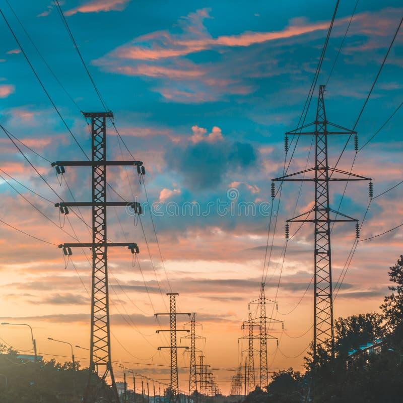 Silhouet van de lijnen van de hoogspanningsmacht tegen een dramatische en kleurrijke hemel bij zonsopgang of zonsondergang royalty-vrije stock foto's