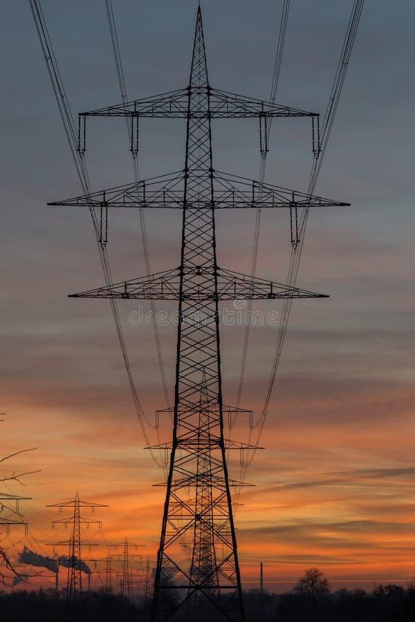 Silhouet van de lijnen van de hoogspanningsmacht tegen een zonsonderganghemel stock foto