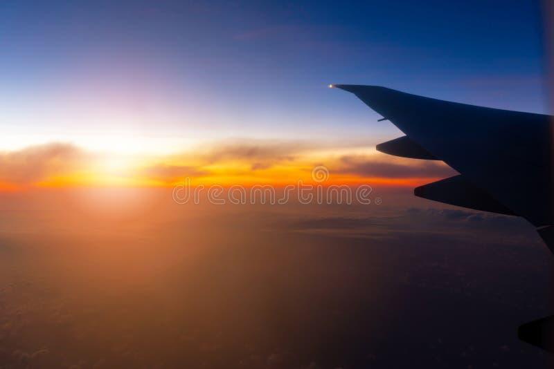 Silhouet van de mening van de Vliegtuigvleugel uit het venster het de bewolkte achtergrond van de zonsonderganghemel, de Reis en  stock afbeeldingen