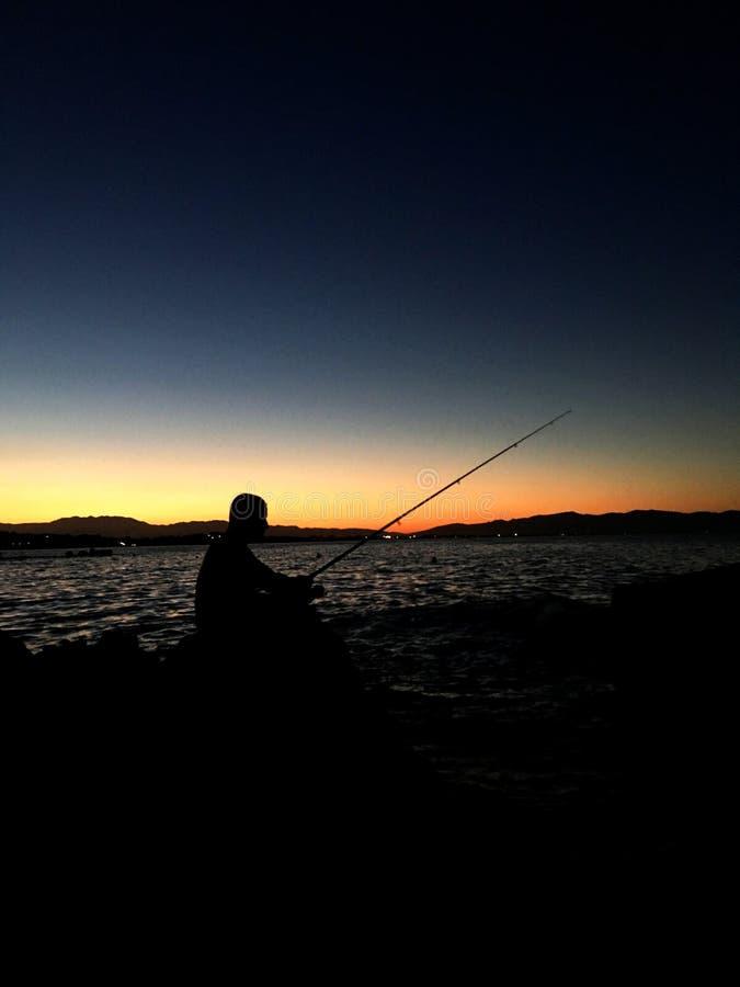 Silhouet van de mens die met hengel tijdens zonsondergang vissen royalty-vrije stock fotografie