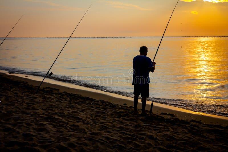 Silhouet van de mens die op het strand in zonsopgangochtend vist royalty-vrije stock afbeeldingen