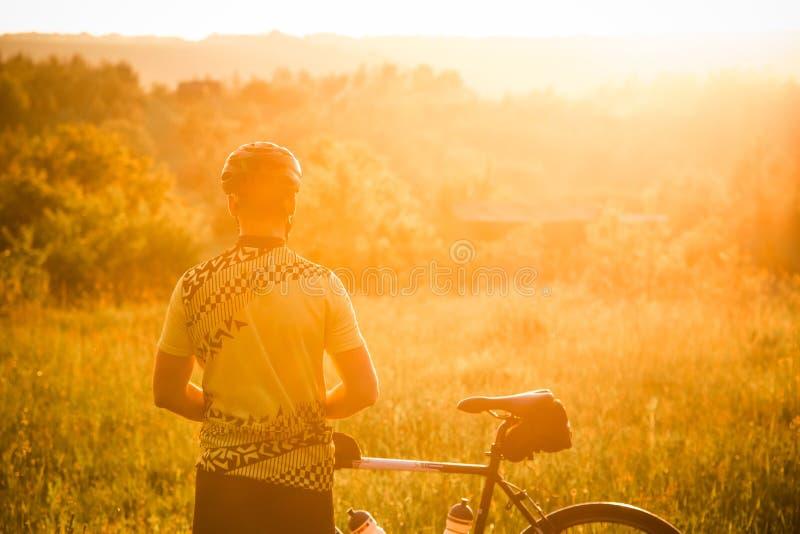 Silhouet van de mens met een fiets De man die voor zonsondergang let op stock fotografie