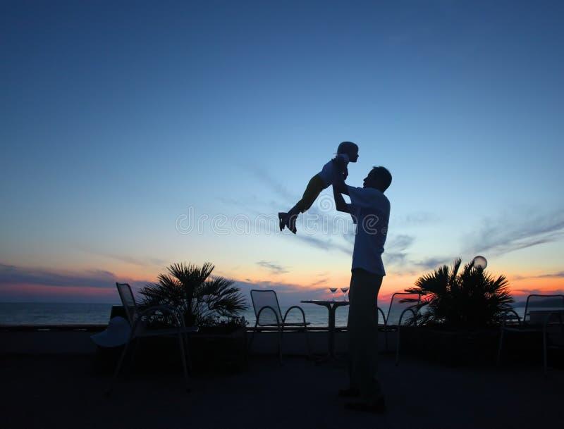Silhouet van de mens met kind in handen op zonsondergang stock foto