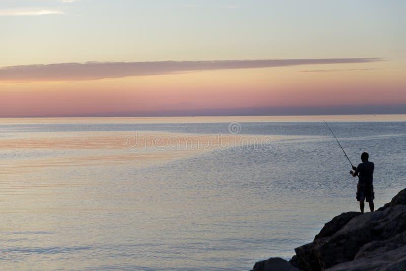 Silhouet van de mens met visserij het spinnen Visserij op het meer bij mooie zonsondergang Meer Ontario Rochester, de V.S. royalty-vrije stock afbeeldingen