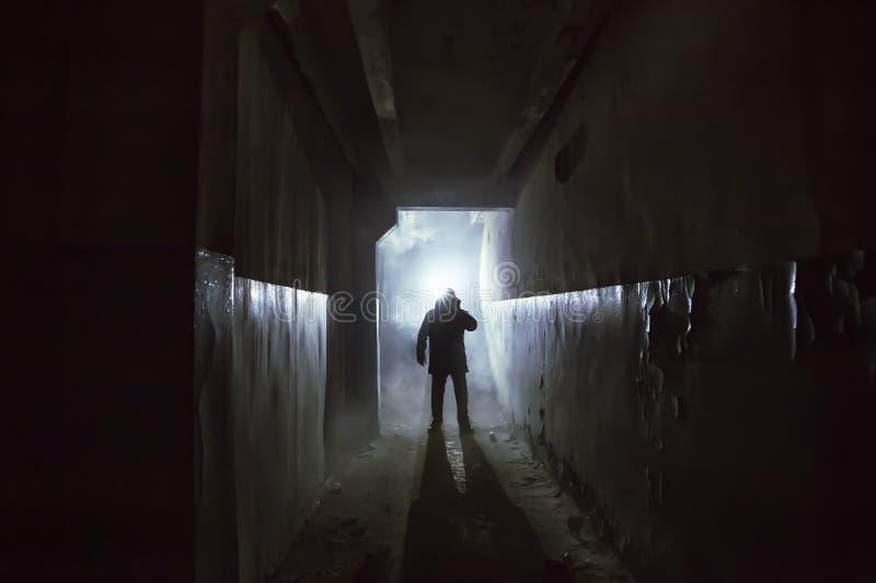 Silhouet van de mens in status in donkere enge gang of tunnel met achterlicht stock foto's