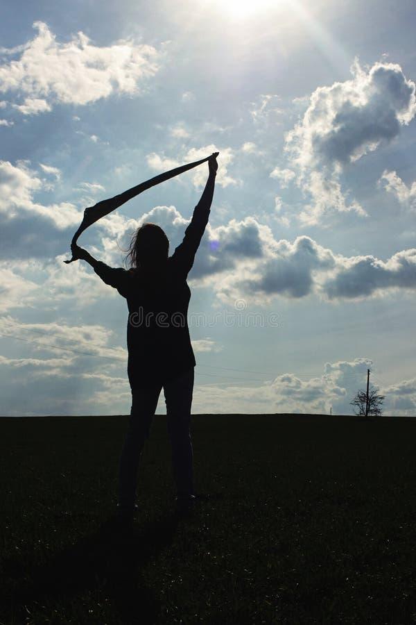 Silhouet van de modieuze sjaal van de meisjesholding in winderige avondou stock fotografie
