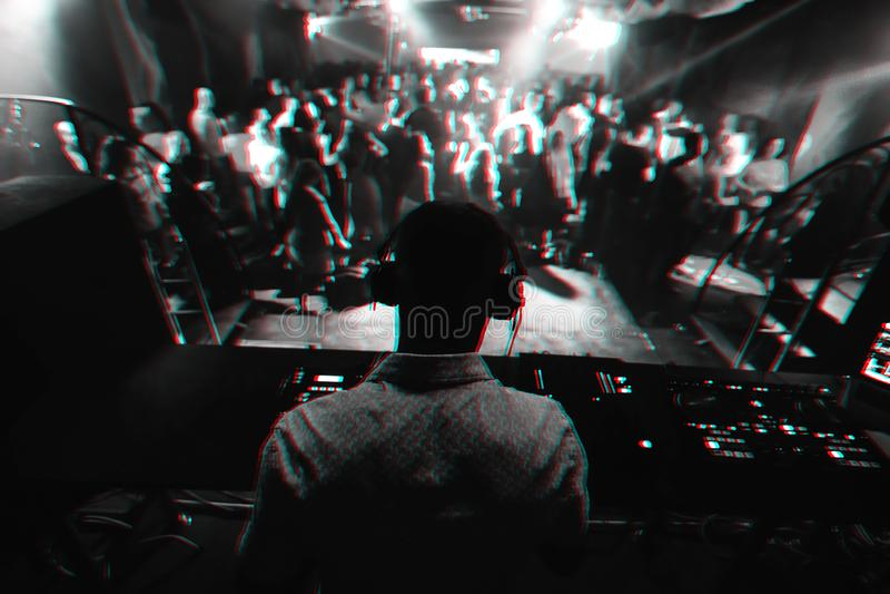 Silhouet van de speelmuziek van DJ op mixer en heel wat mensen die in nachtclub op stadium dansen royalty-vrije stock afbeeldingen