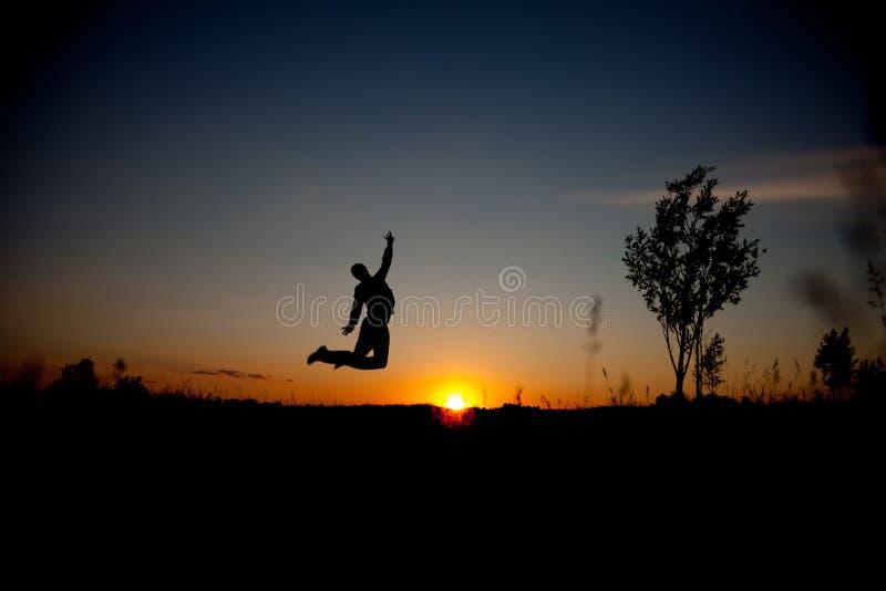 Silhouet van de springende mens en mooie zonsonderganghemel Element van ontwerp Bedrijfs concept royalty-vrije stock foto's