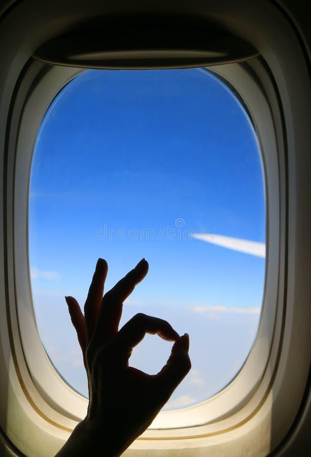 Silhouet van de vrouwelijke hand die van ` s O.K. teken stellen tegen vliegtuigvenster met trillende blauwe hemel en vliegtuigvle stock foto