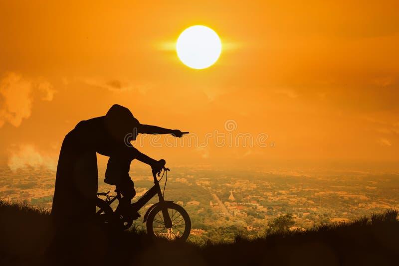 Silhouet van de zoon van het Moederonderwijs het biking stock fotografie