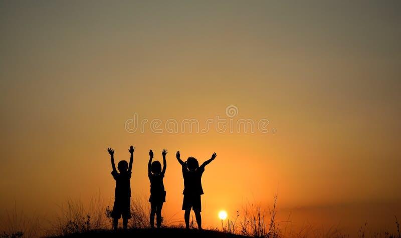 Silhouet van drie kinderenvriendschap bij zonsondergang Mensenvrienden stock foto