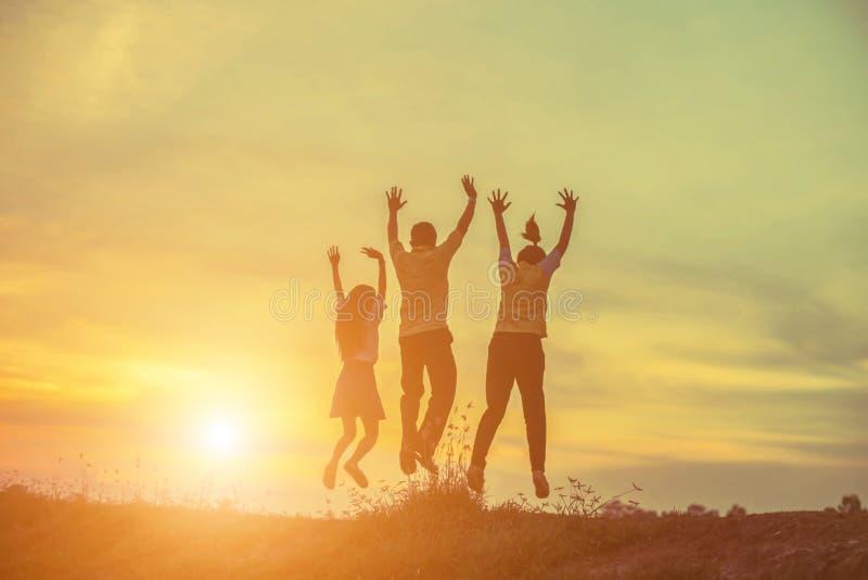 Silhouet van Drie mensen die omhoog samen bij zonsondergang springen stock foto