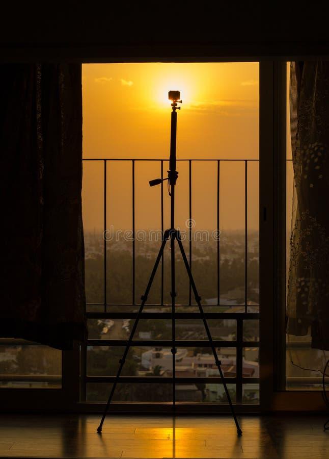 Silhouet van een actiecamera opgezet op een driepoot voor het nemen van een tijdtijdspanne van een zonsondergang of een zonsopgan royalty-vrije stock afbeeldingen
