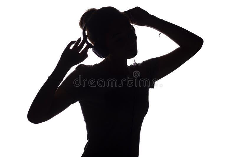 Silhouet van een actief meisje die aan muziek in hoofdtelefoons luisteren, cijfer van het jonge vrouw dansen met handen omhoog op stock afbeelding