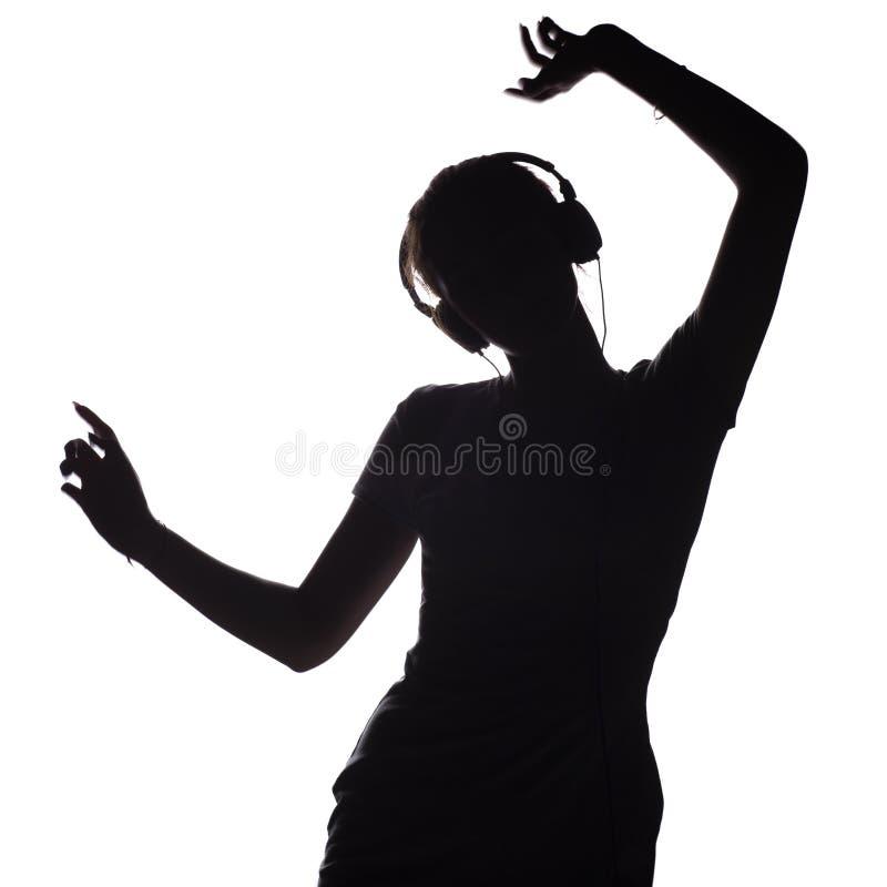 Silhouet van een actief meisje die aan muziek in hoofdtelefoons luisteren, cijfer van het jonge vrouw dansen met handen omhoog op royalty-vrije stock afbeelding