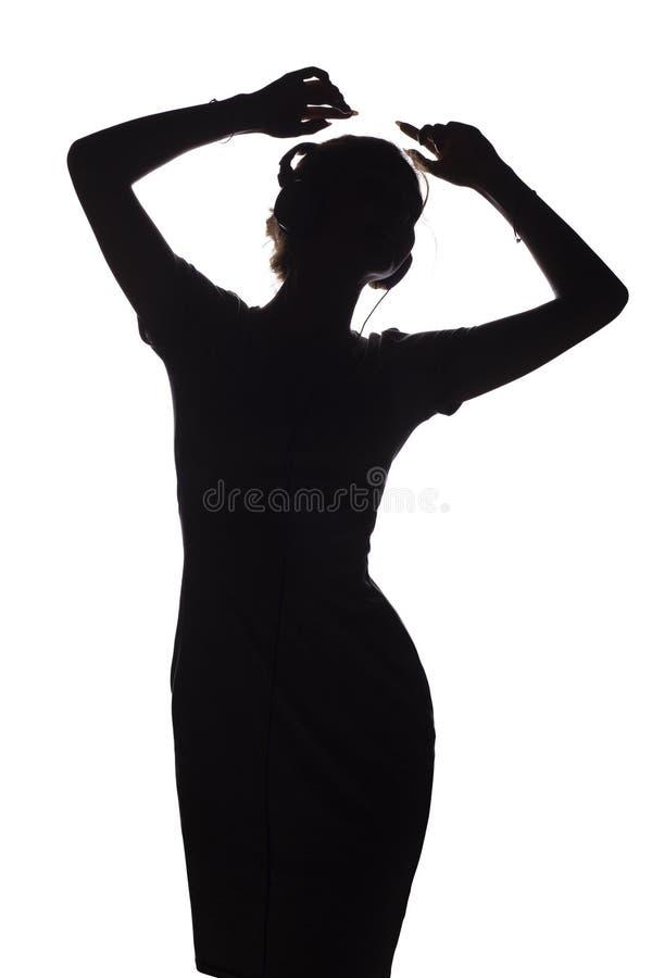 Silhouet van een actief meisje die aan muziek in hoofdtelefoons luisteren, cijfer van het jonge vrouw dansen met handen omhoog op royalty-vrije stock afbeeldingen