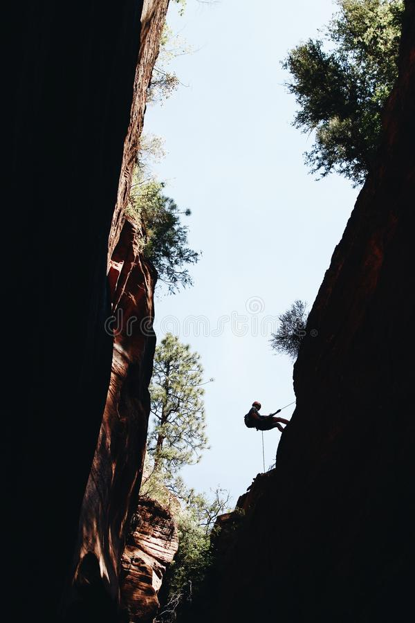 Silhouet van een alpinist die een rots beklimmen tijdens dag in Zion National Park, de V.S. stock afbeeldingen