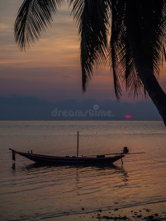 Silhouet van een boot en palmen tegen de het plaatsen zon met wolken royalty-vrije stock afbeeldingen