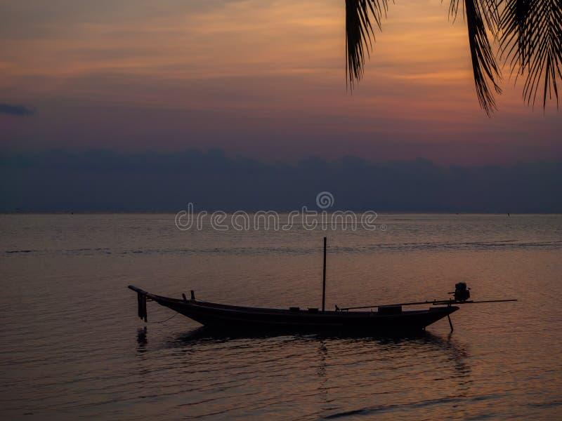Silhouet van een boot en palmen tegen de het plaatsen zon met wolken stock afbeelding