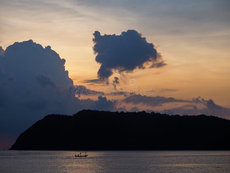 Silhouet van een boot op de achtergrond van de het plaatsen zon met wolken stock foto