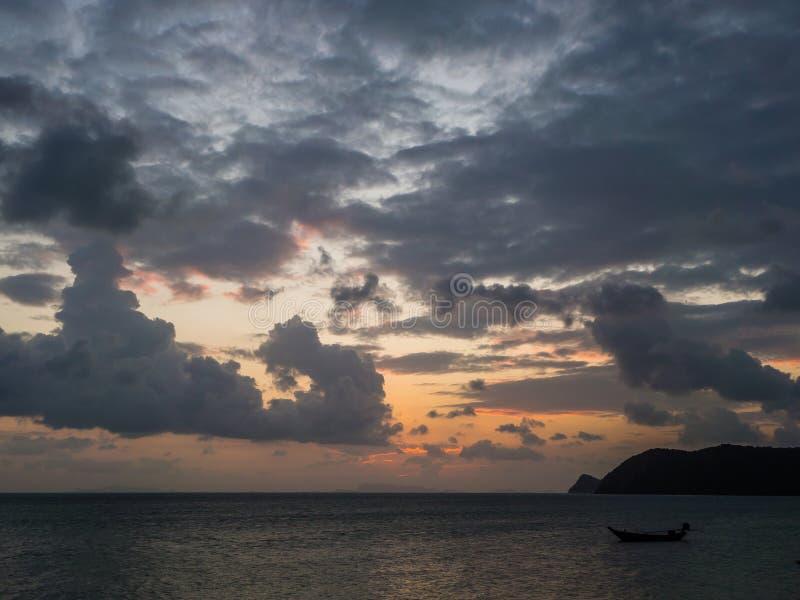 Silhouet van een boot op de achtergrond van de het plaatsen zon met wolken stock foto's