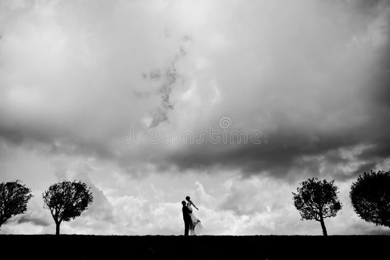 Silhouet van een bruid en een bruidegom op de horizon stock foto