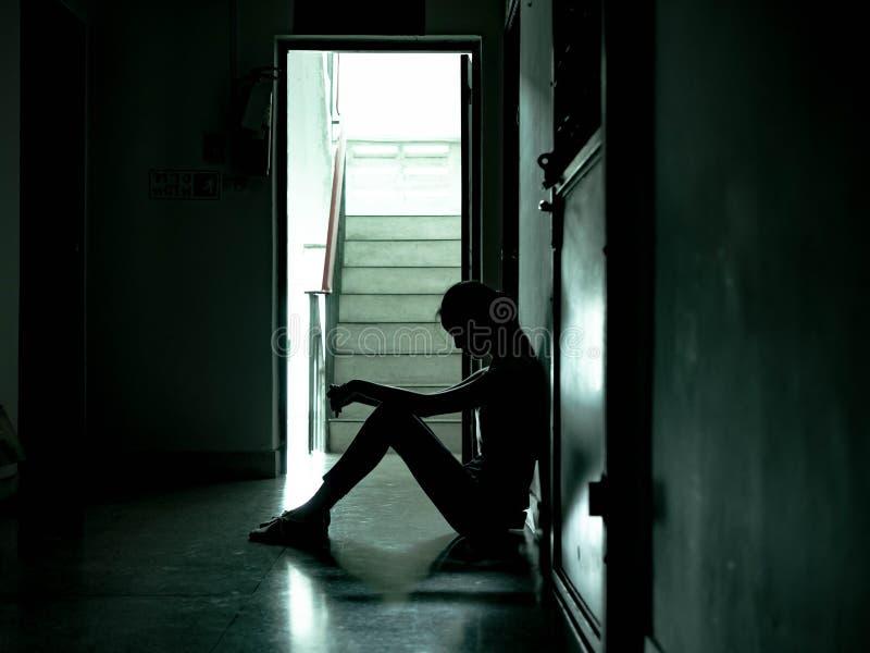 Silhouet van een droevige jonge meisjeszitting in het donkere leunen tegen de muur, Huiselijk geweld, familieproblemen, Spanning, royalty-vrije stock afbeeldingen