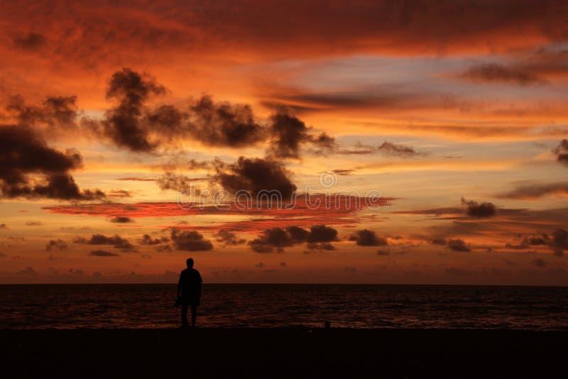 Silhouet van een eenzame mens op een strand bij schemer stock afbeelding