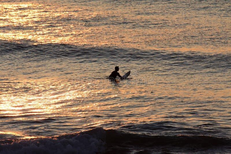 Silhouet van een eenzame surfer die op een golf dichtbij het strand bij zonsondergang wachten stock foto's