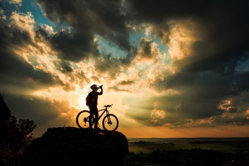 Silhouet van een fietser en een fiets op hemelachtergrond stock afbeeldingen