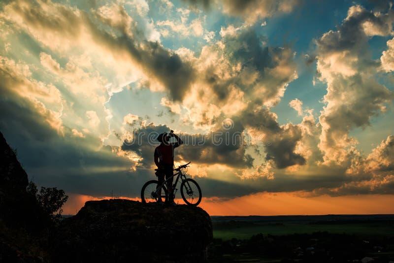 Silhouet van een fietser en een fiets op hemelachtergrond royalty-vrije stock afbeelding