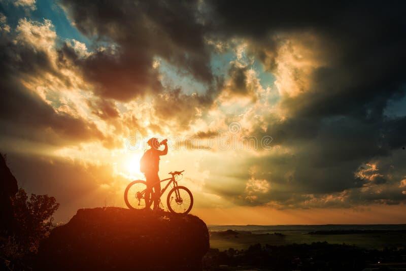 Silhouet van een fietser en een fiets op hemelachtergrond stock foto's