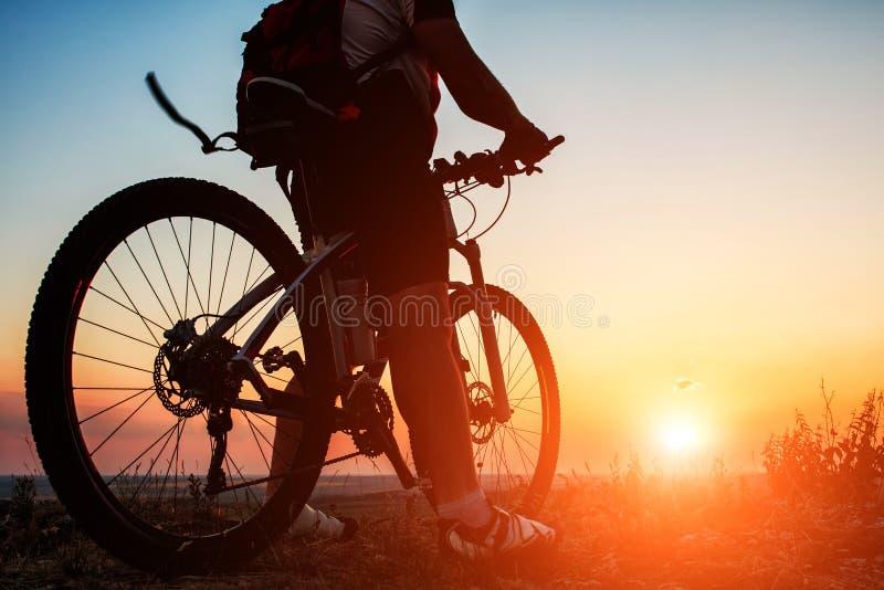 Silhouet van een fietser en een fiets op hemelachtergrond royalty-vrije stock afbeeldingen