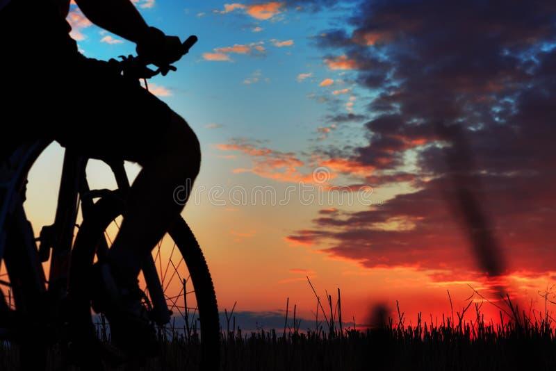 Silhouet van een fietser en een fiets op zonsondergangachtergrond stock foto's