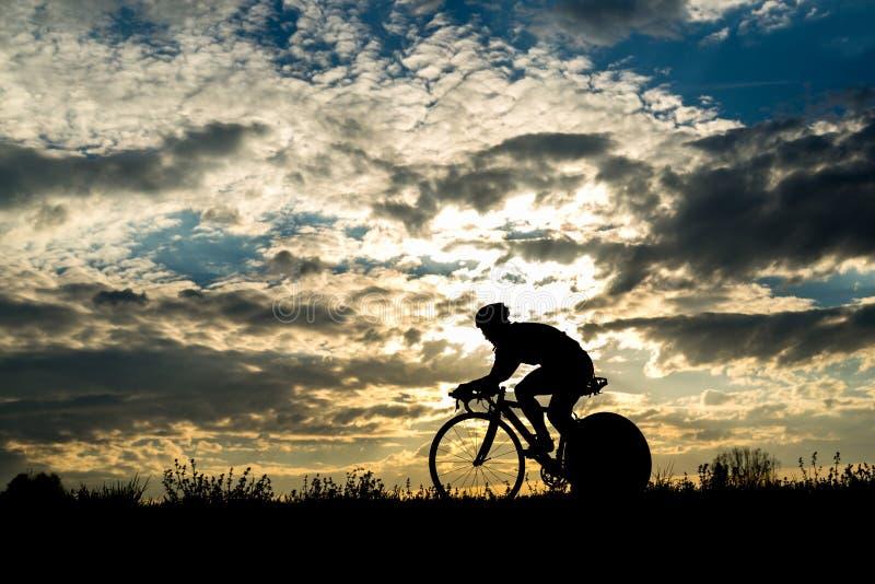 Silhouet van een fietser in zonsondergang stock foto