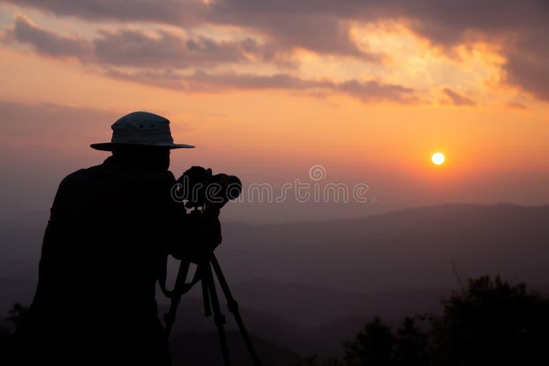 Silhouet van een fotograaf die een zonsondergang in de bergen schiet stock afbeeldingen