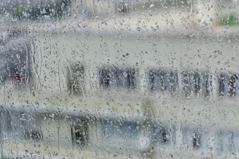 Silhouet van een gebouw met meerdere verdiepingen met witte muren en vensters op de achtergrond van een nat glas met regenstroken stock afbeelding