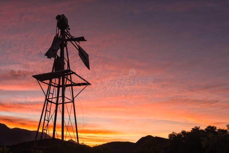 Silhouet van een gebroken windmolen tegen zonsondergang stock afbeeldingen