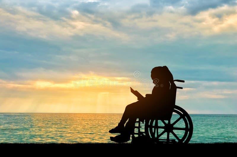 Silhouet van een gehandicapte zitting van het kindmeisje in een rolstoel die een boek op een overzeese zonsondergangachtergrond l stock foto's