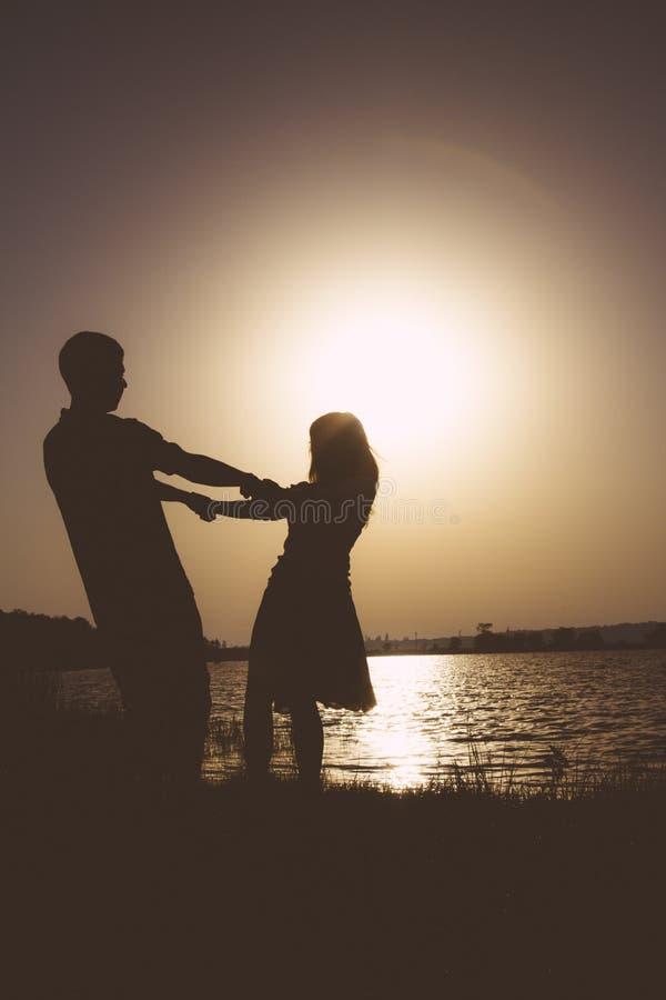 Silhouet van een gelukkig jong paar die bij dageraad op aard spinnen royalty-vrije stock afbeelding