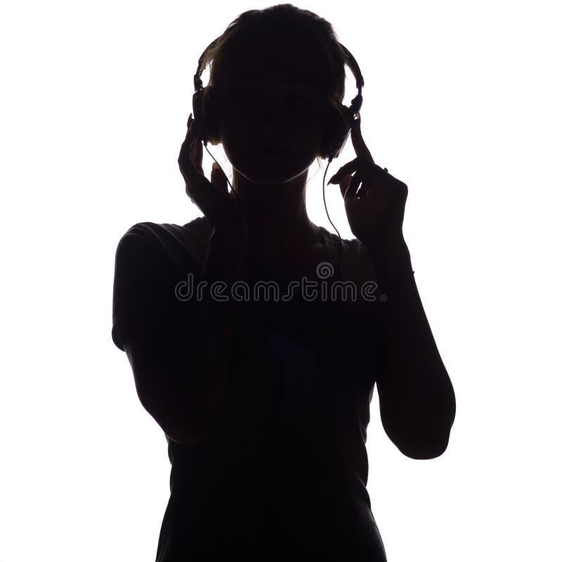 Silhouet van een gelukkig meisje die aan muziek in hoofdtelefoons luisteren, cijfer van jonge vrouw met handen die omhoog op een  royalty-vrije stock afbeeldingen