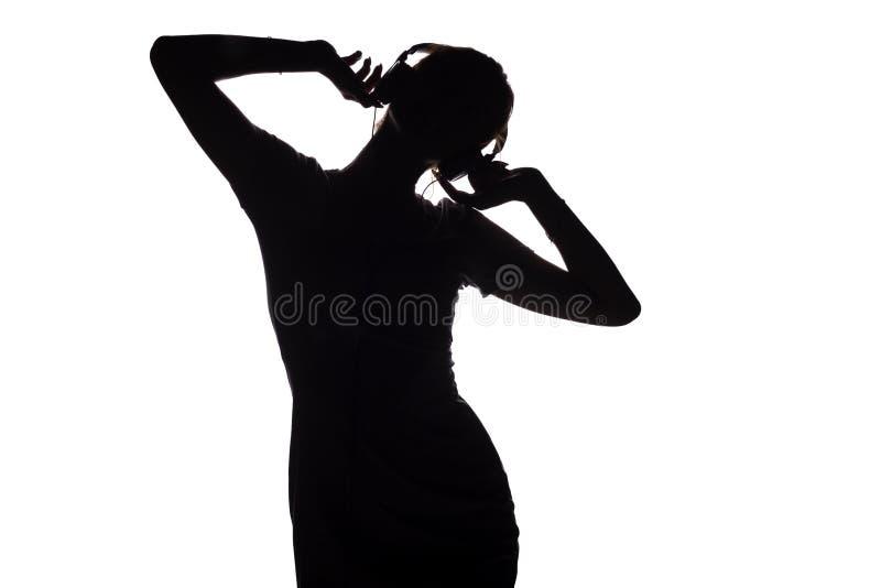 Silhouet van een gelukkig meisje die aan muziek in hoofdtelefoons luisteren, cijfer van jonge vrouw met handen die omhoog op een  stock afbeeldingen