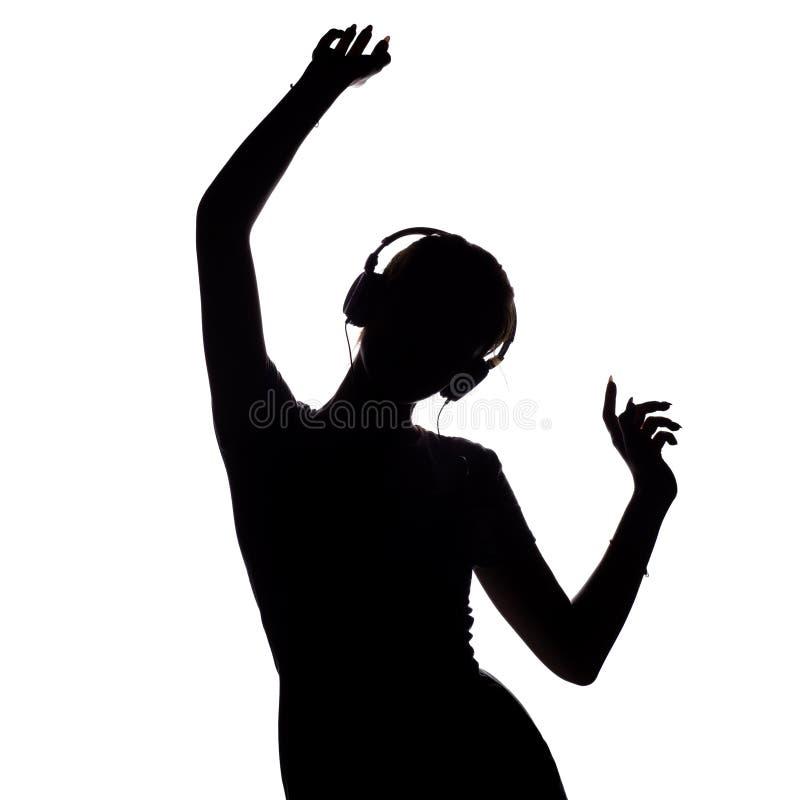 Silhouet van een gelukkig meisje die aan muziek in hoofdtelefoons luisteren, cijfer van jonge vrouw met handen die omhoog op een  stock foto