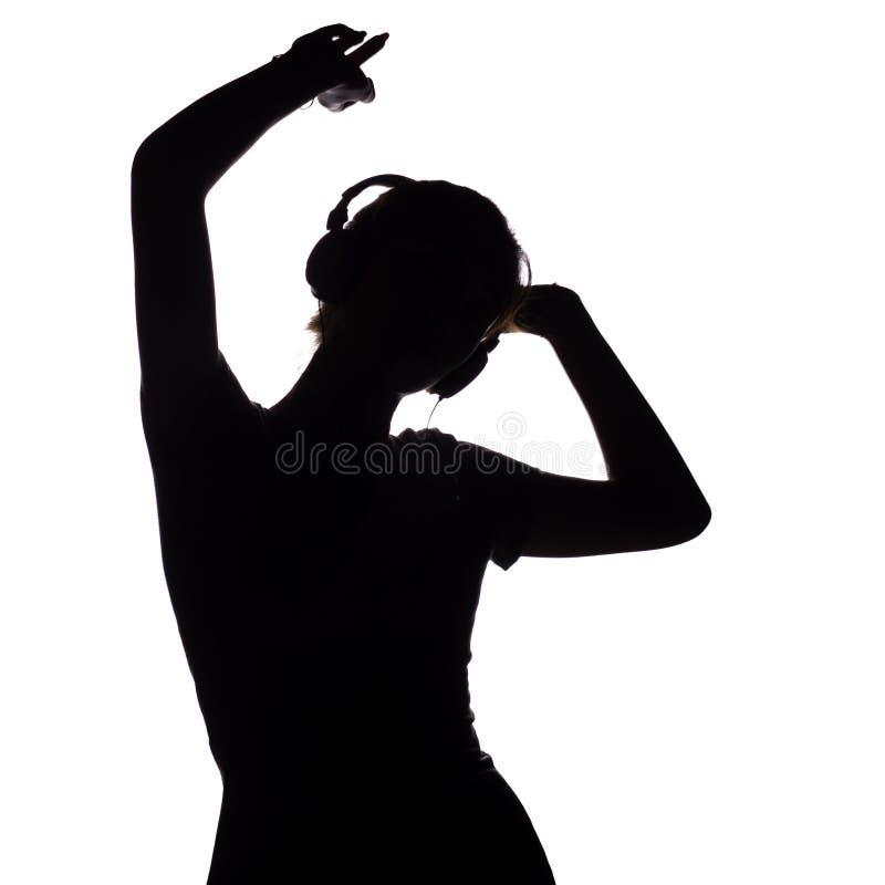 Silhouet van een gelukkig meisje die aan muziek in hoofdtelefoons luisteren, cijfer van jonge vrouw met handen die omhoog op een  royalty-vrije stock foto's