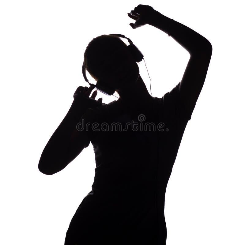 Silhouet van een gelukkig meisje die aan muziek in hoofdtelefoons luisteren, cijfer van jonge vrouw met handen die omhoog op een  stock foto's
