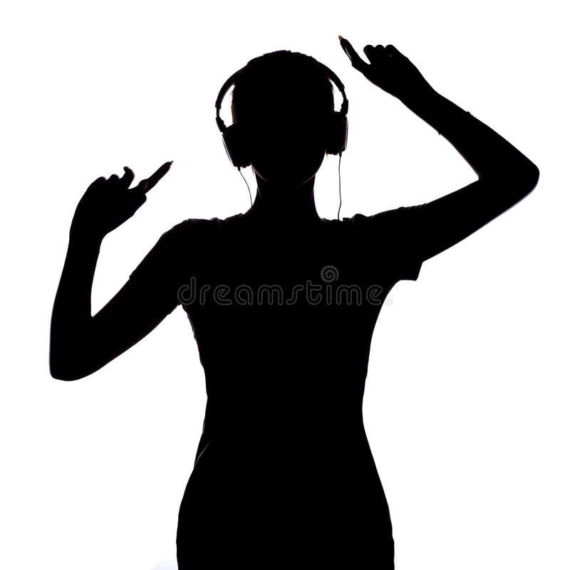 Silhouet van een gelukkig meisje die aan muziek in hoofdtelefoons luisteren, cijfer van jonge vrouw met handen die omhoog op een  stock fotografie