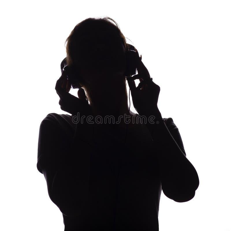 Silhouet van een gelukkig meisje het luisteren lied en het ontspannen in hoofdtelefoons, cijfer die van tennager zich aan de muzi royalty-vrije stock fotografie