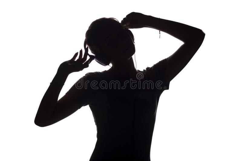 Silhouet van een gelukkig meisje het luisteren lied en het ontspannen in hoofdtelefoons, cijfer die van tennager zich aan de muzi stock foto's